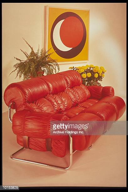 BROWN LEATHER SOFA WITH PLANTS AND A PAINTING