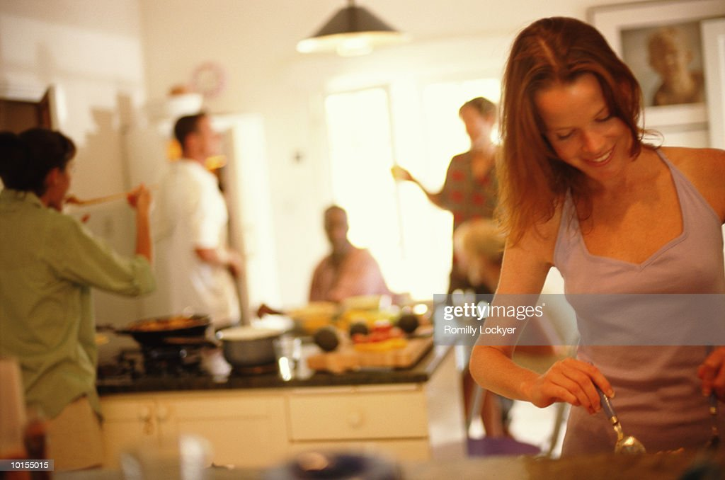 WOMAN PREPARING FOOD WITH FRIENDS : Stock Photo