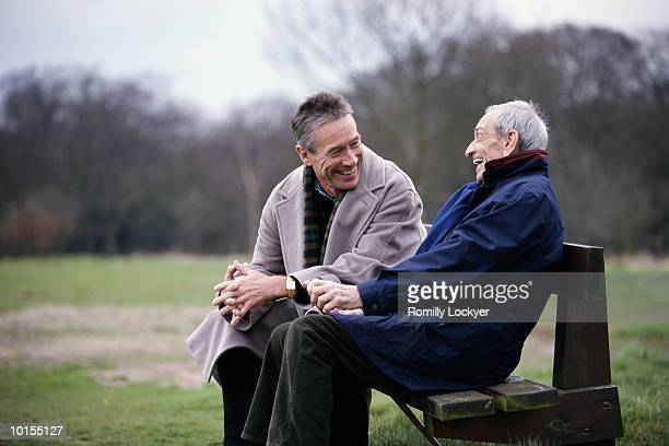 80S FATHER WITH 50S SON ON PARK BENCH