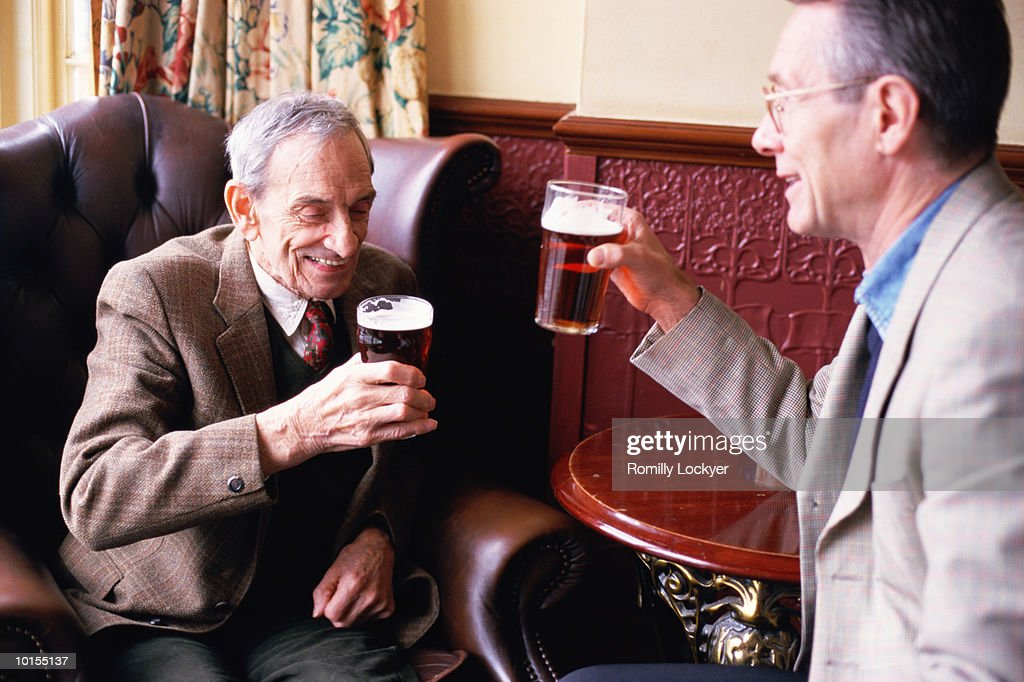80S FATHER WITH 50S SON DRINKING IN PUB : Stock Photo