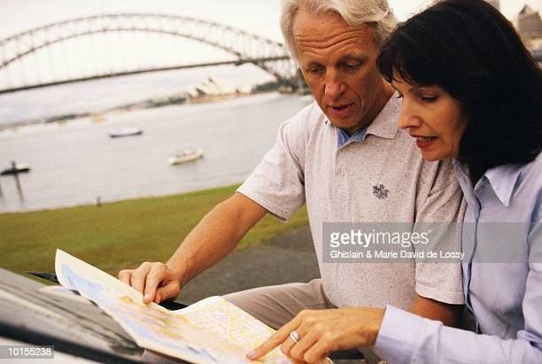 MIDDLE AGED COUPLE LOOKING AT MAP