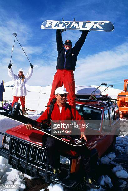 SNOWBOARDERS ON TOP OF CAR