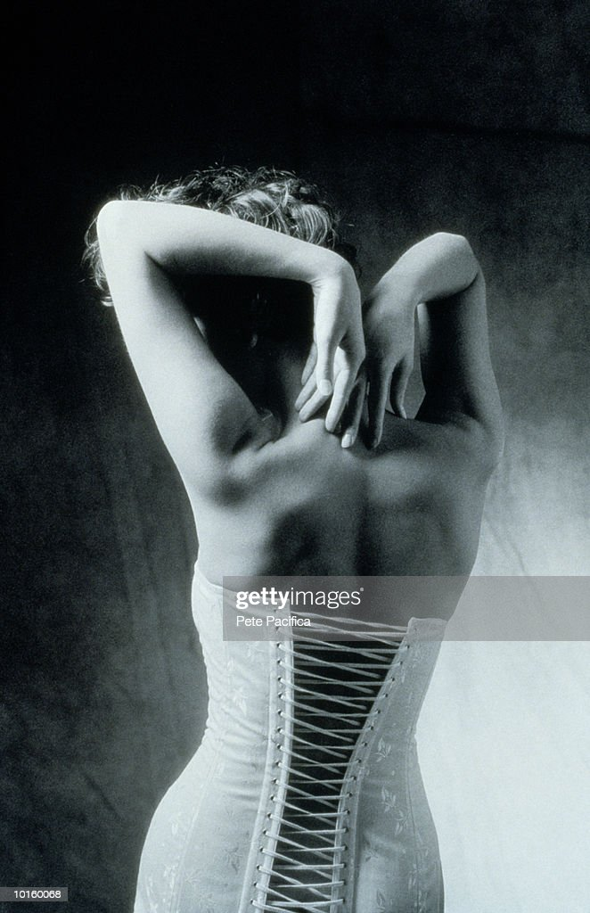 YOUNG WOMANS BACK WEARING CORSET : Stock Photo