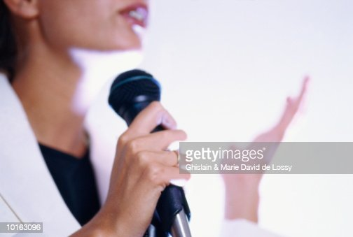 WOMAN HOLDING MICROPHONE : Stock Photo