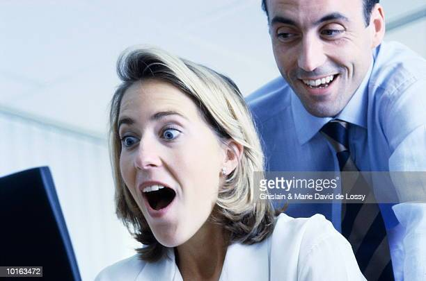 BUSINESS MAN AND WOMAN IN FRONT OF COMPUTER