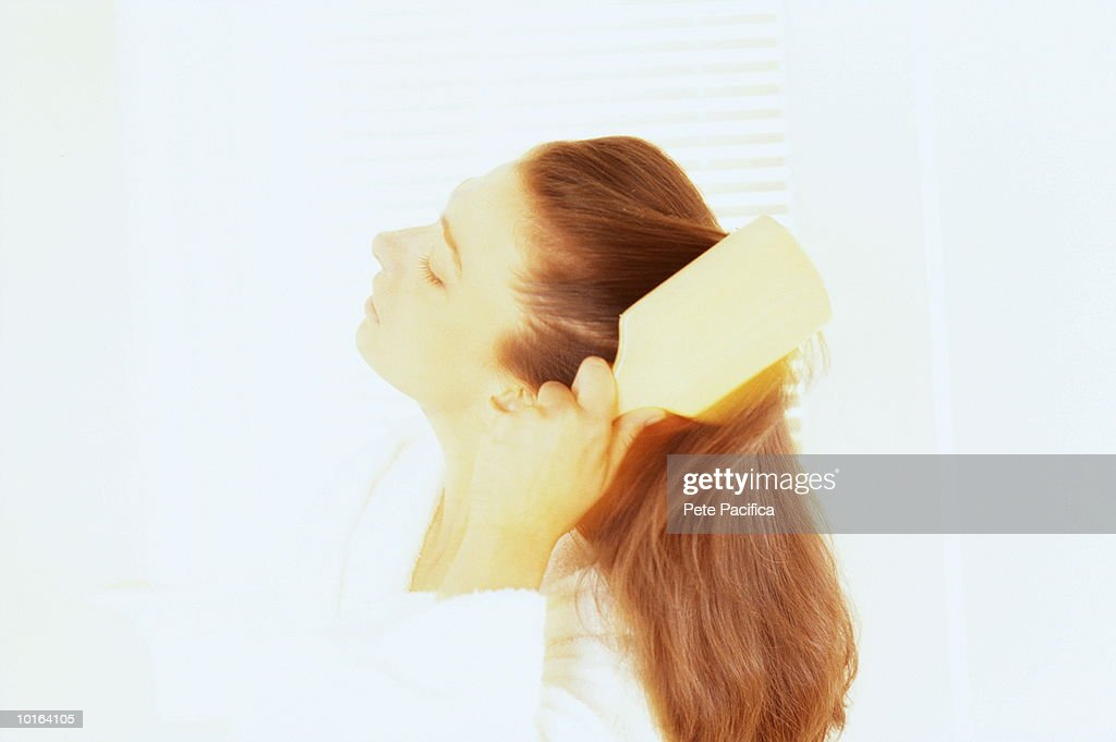 WOMAN IN BATHROOM BRUSHING HAIR : Stock Photo