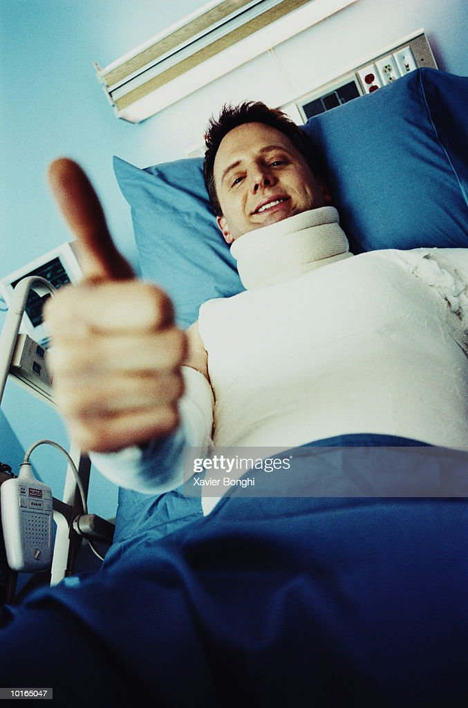 man in body cast giving thumbs up stock photo getty images