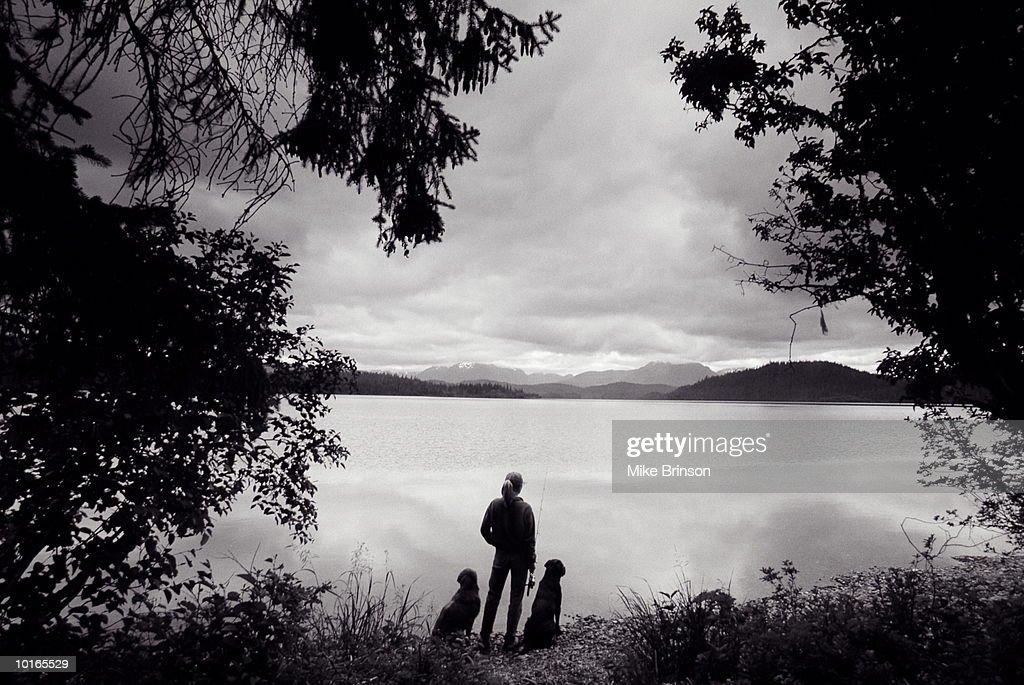 FISHERWOMAN WITH DOGS AT LAKE, JUNEAU, ALASKA : Stock Photo