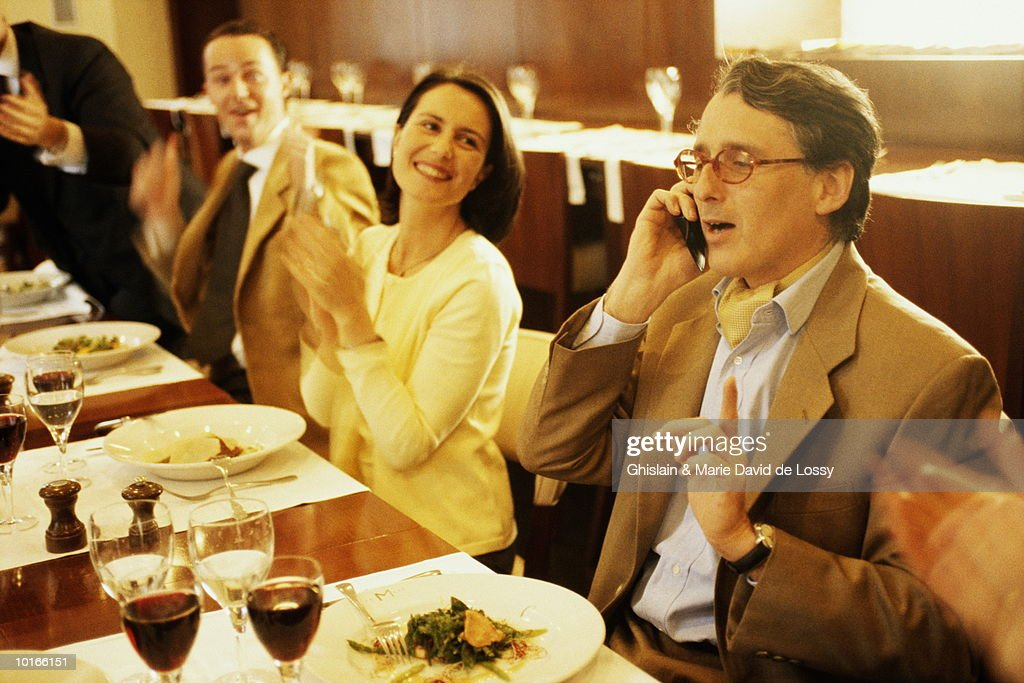 MAN ON CELLULAR PHONE BEING APPLAUDED : Stock Photo