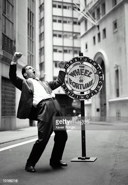 BUSINESSMAN WITH WHEEL OF FORTUNE