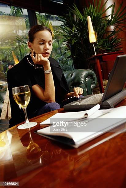 BUSINESSWOMAN SITTING IN HOTEL WITH LAPTOP