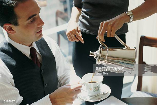 WOMAN SERVING COFFEE TO BUSINESSMAN