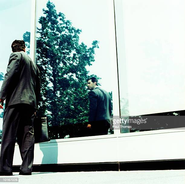 BUSINESSMAN CHECKING APPEARANCE IN WINDOW