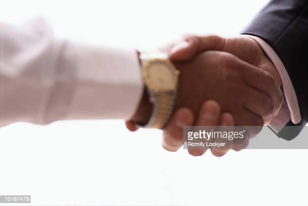 BUSINESSMEN SHAKE HANDS, CLOSE-UP