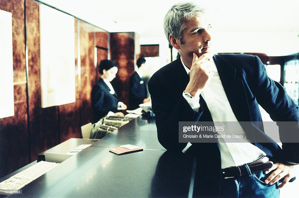 MAN CHECKING IN AT HOTEL RECEPTION : Stock Photo