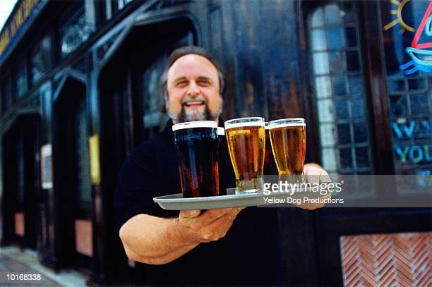 PUB OWNER WITH TRAY OF BEER