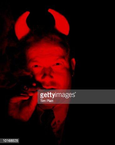 DEVIL BUSINESSMAN SMOKING CIGAR : Stock Photo