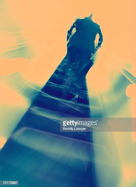 BUSINESSMAN ASCENDING ESCALATOR
