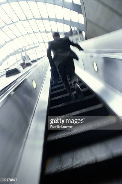COMMUTER RUNNING UP ESCALATOR