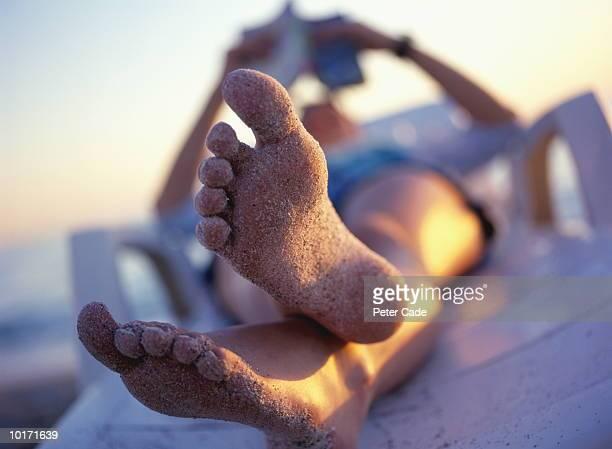 TEENAGE GIRL LYING ON LOUNGER, SUNSET