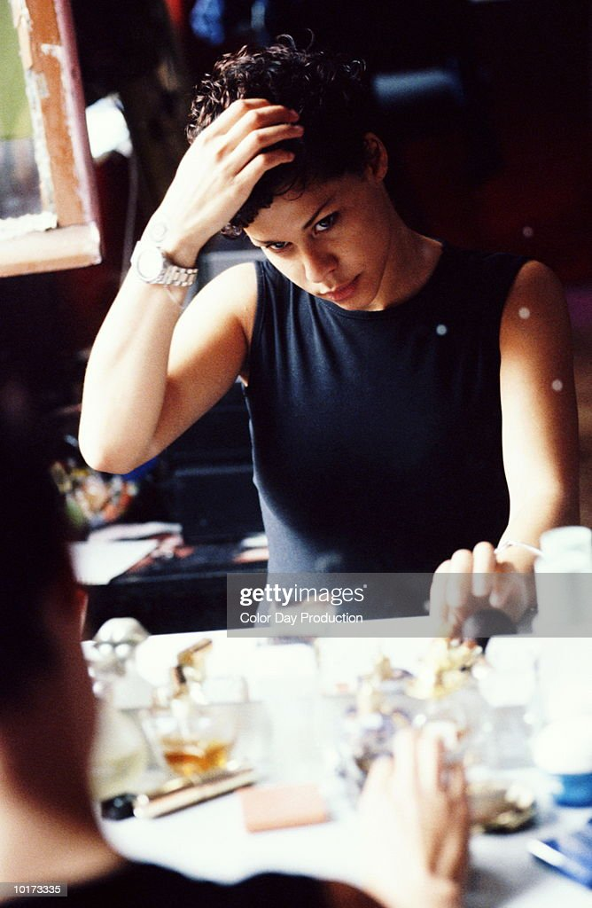YOUNG WOMAN LOOKING IN MIRROR : Stock Photo