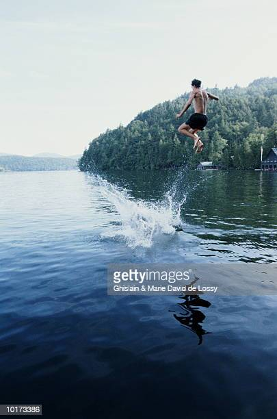 YOUNG MAN LEAPING INTO SPLASHING WATER