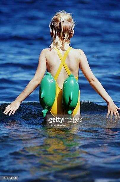 GIRL WEARING FLOTATION GEAR IN OCEAN