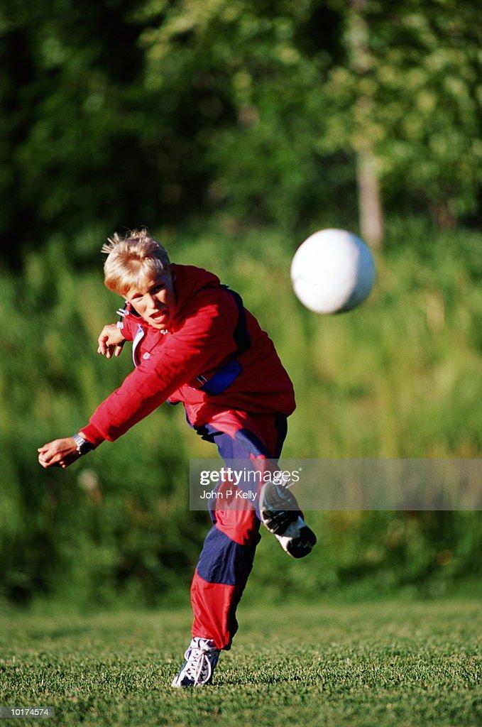 YOUNG BOY KICKING SOCCER BALL : Stock Photo
