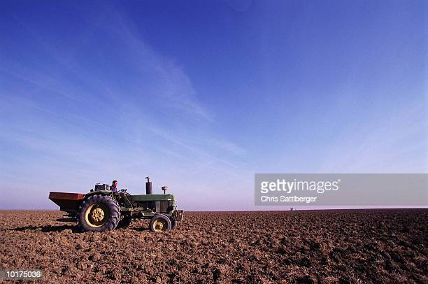 FARMER SOWING FIELD WITH TRACTOR