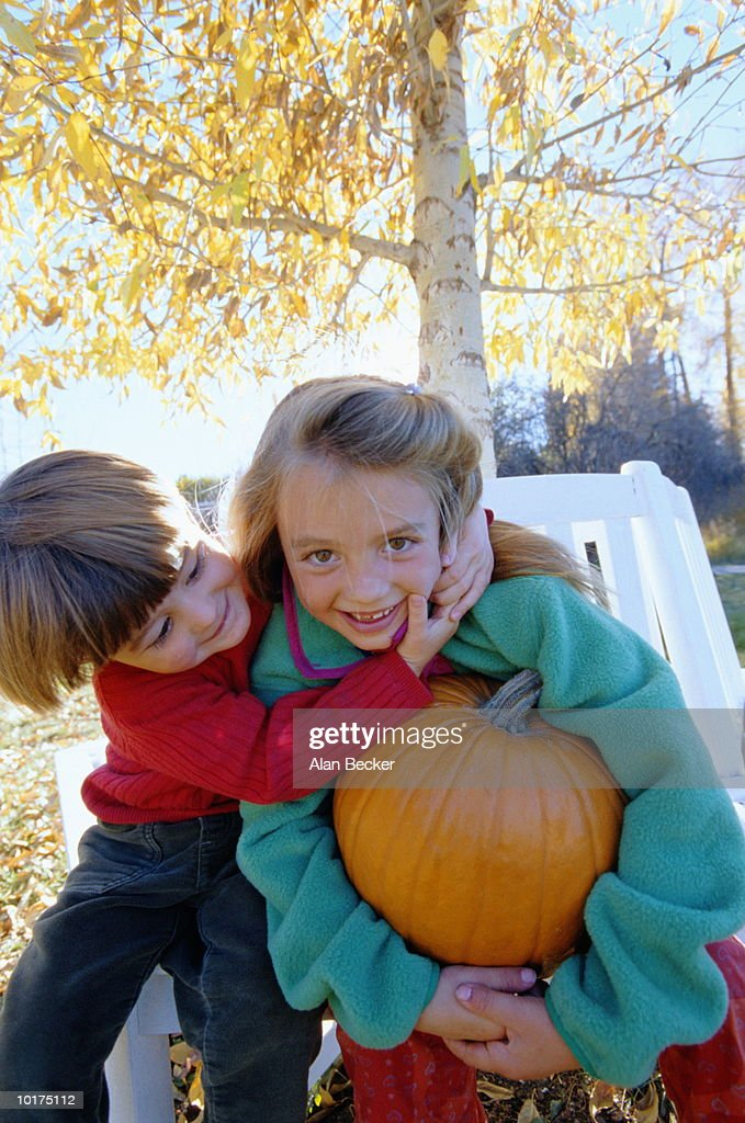 YOUNG GIRL AND BOY WITH PUMPKIN : Stock Photo