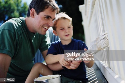 FATHER SHOWING SON HOW TO PAINT FENCE : Stock Photo