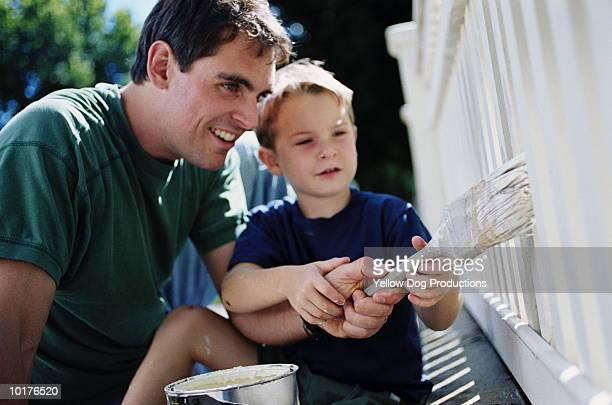 FATHER SHOWING SON HOW TO PAINT FENCE