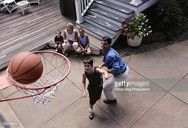 FATHER AND SON PLAYING BASKETBALL, OUTDOORS