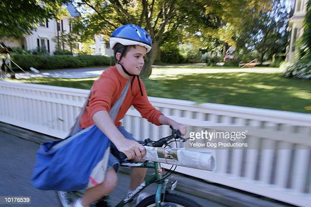 PAPERBOY DELIVERING NEWSPAPERS ON BIKE