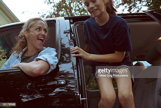GIRL CLIMBING OUT OF CAR, MOM WATCHING