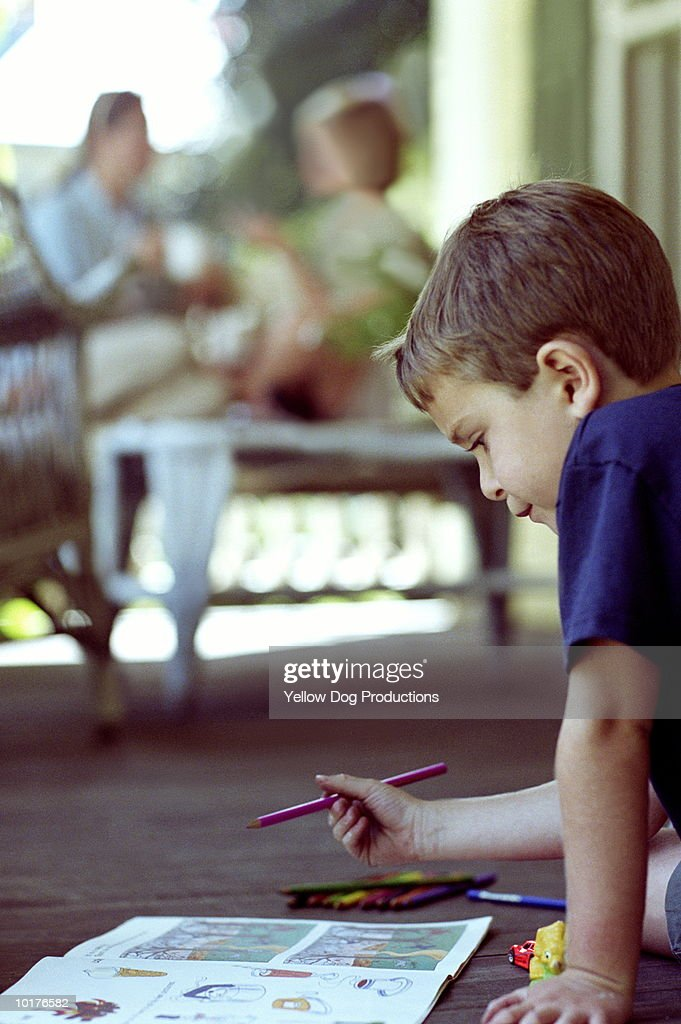 BOY COLORING WITH MOM AND FRIEND IN BACKGROUND : Stock Photo