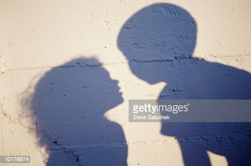 SHADOWS OF YOUNG BOY & GIRL ON WALL : Stock Photo