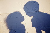 SHADOWS OF YOUNG BOY & GIRL ON WALL