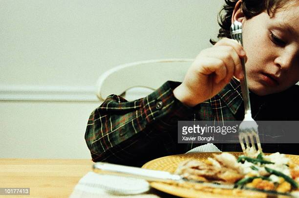 BOY  ALONE AT DINNER TABLE, PICKING AT FOOD