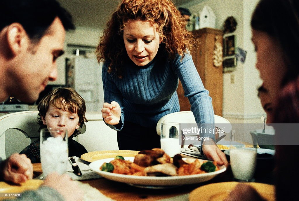 MOM PUTTING FOOD ON DINNER TABLE : Stock Photo