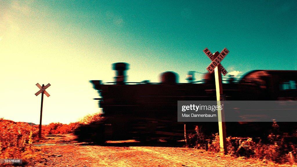 STEAM ENGINE TRAIN AT RAILROAD CROSSING : Stock Photo