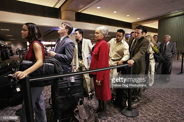 PEOPLE IN LINE AT AIRPORT TICKET COUNTER
