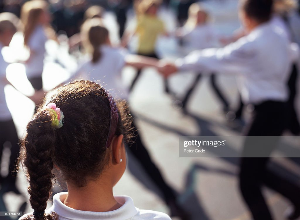 GIRL WATCHING OTHER CHILDREN PLAYING : Stock Photo