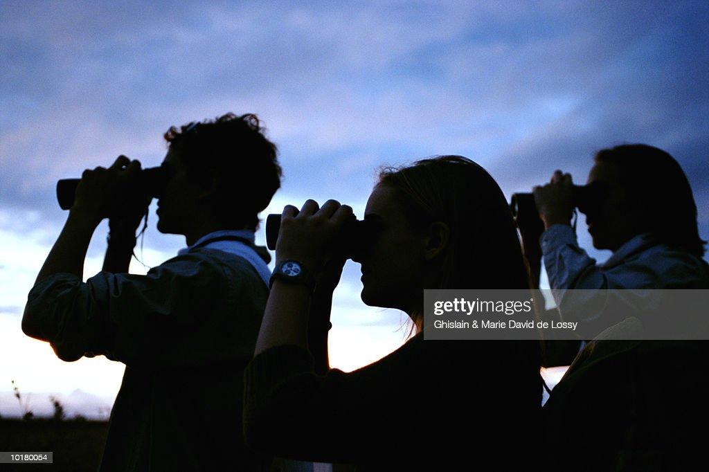 PEOPLE LOOKING THROUGH BINOCULARS : Stock Photo