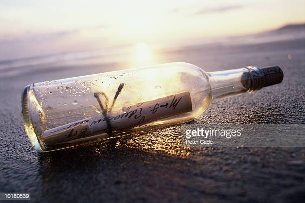 MESSAGE IN BOTTLE ON BEACH AT SUNSET