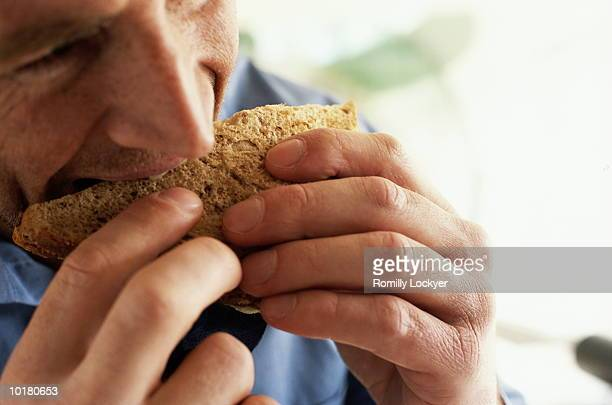 CLOSE UP OF BUSINESS MAN EATING SANDWICH