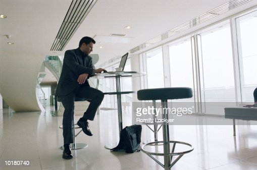 BUSINESSMAN SITTING IN LOUNGE WITH LAPTOP : Stock Photo