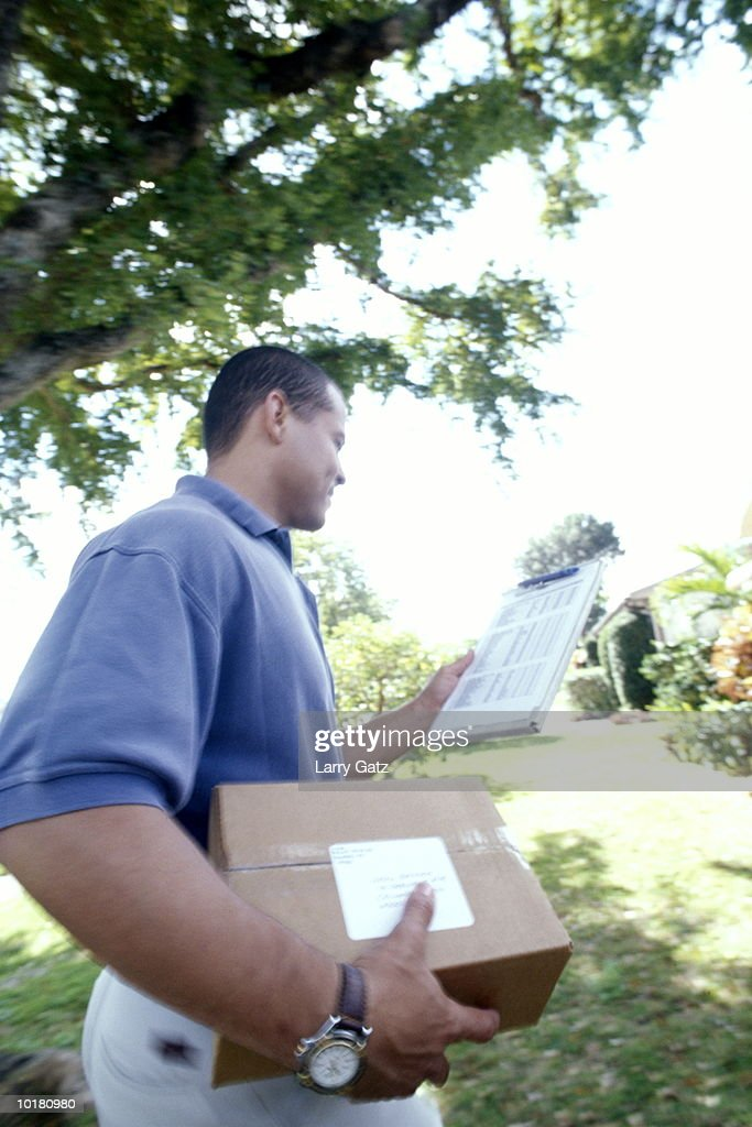 DELIVERY MAN HOLDING PACKAGE & CLIPBOARD : Foto de stock