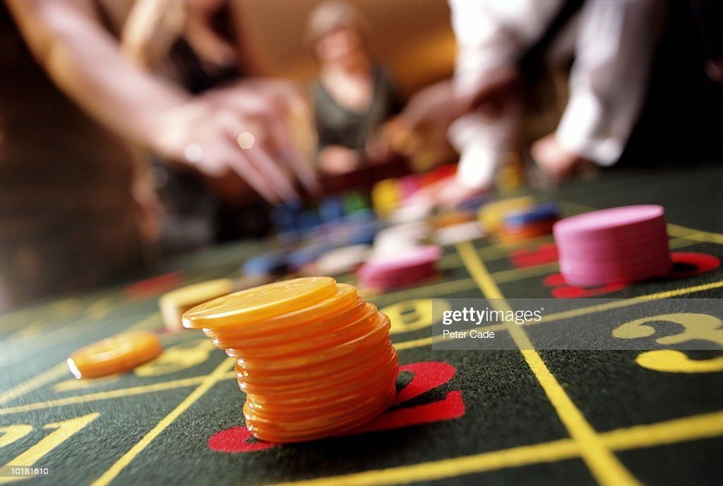 PEOPLE PLACING BETS AT ROULETTE TABLE, CLOSE UP : Stock Photo