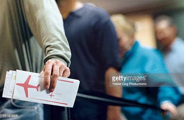 MAN HOLDING TICKET IN AIRLINE CHECK IN LINE